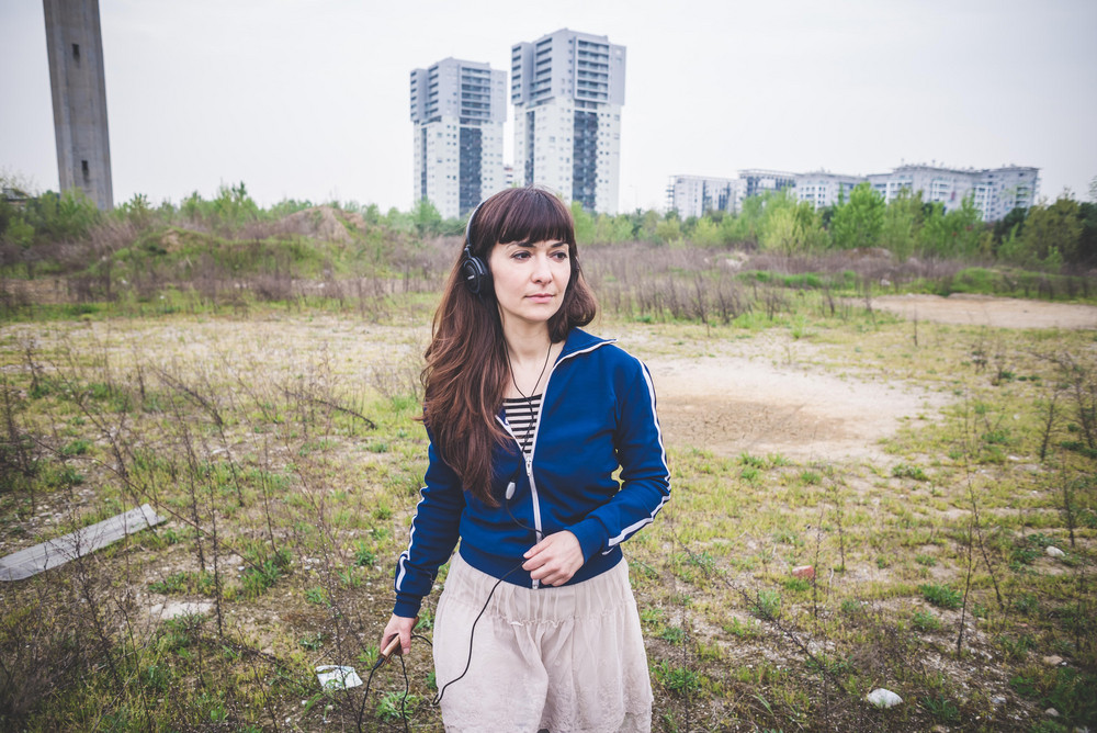 beautiful woman listening music in a desolate lurban landscape