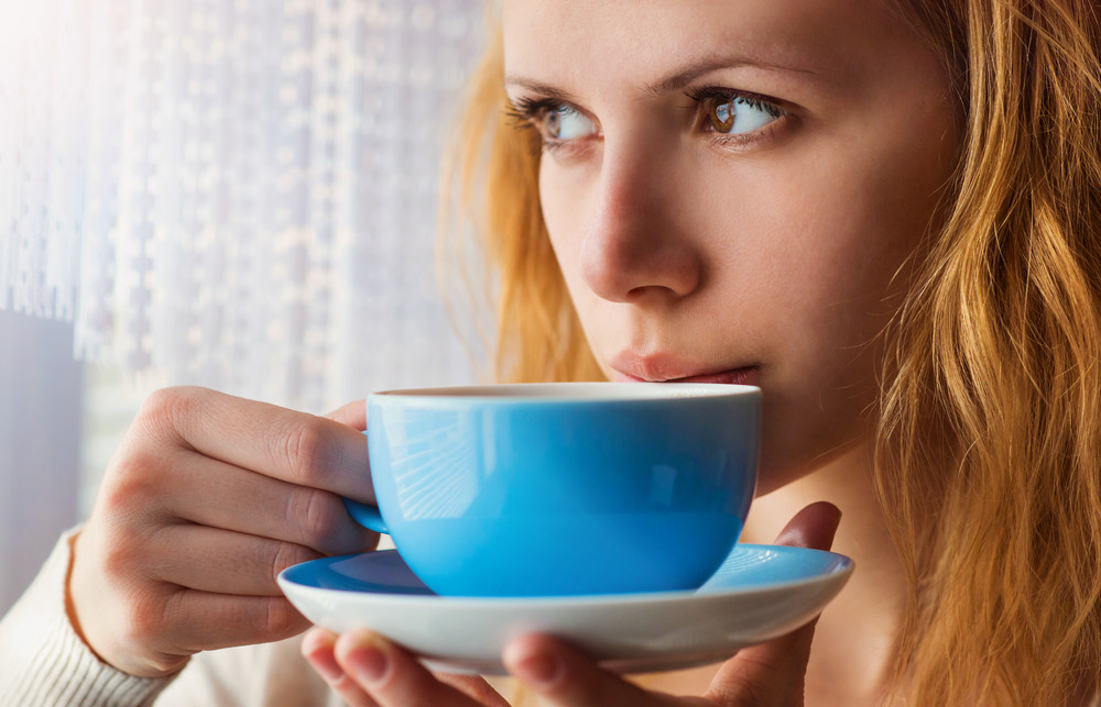 Beautiful woman sipping coffee from her cup