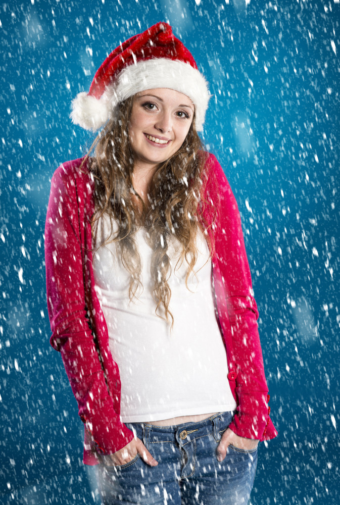 Beautiful woman wearing christmas hat on blue winter background with snowflakes