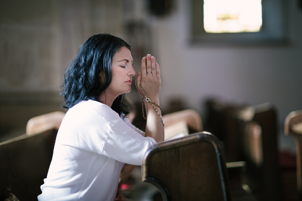 Beautiful woman with a rosary praying in the church