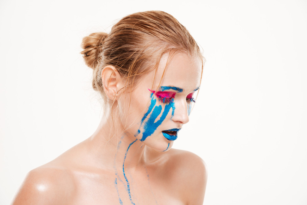 Beautiful woman with blue tears looking down. Color make up. Emotion