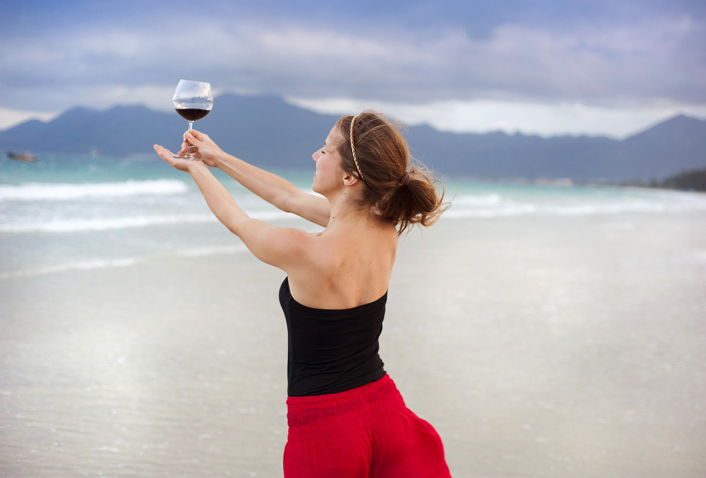 Beautiful woman with glass of red wine is relaxing and enjoying the sea view at the sandy beach