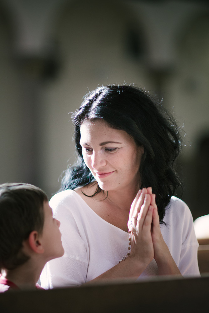Beautiful woman with her son praying in the church