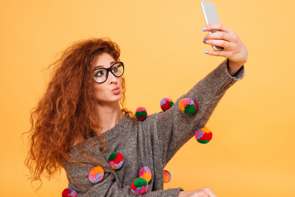 Beautiful woman with long red hair taking selfie photo on smartphone isolated on orange background