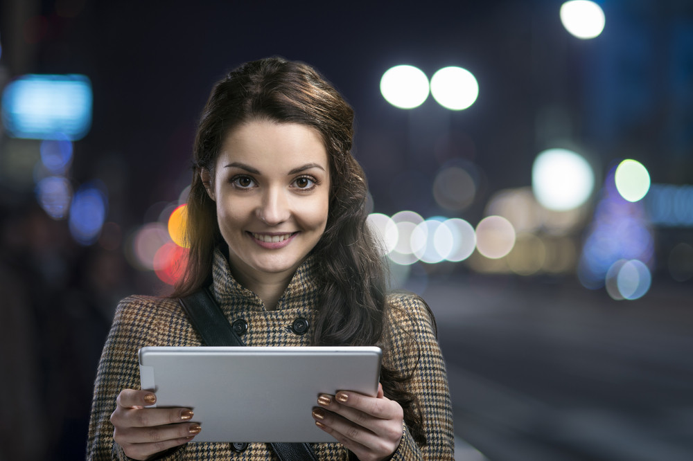 Beautiful woman with tablet outside in the winter night city