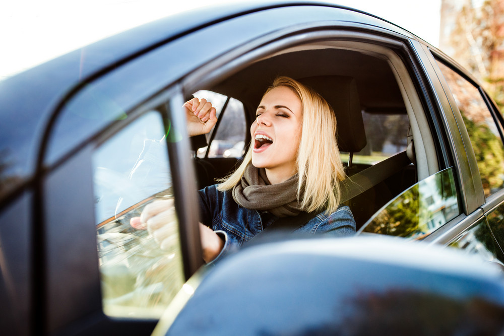 Beautiful young blond woman driving a car