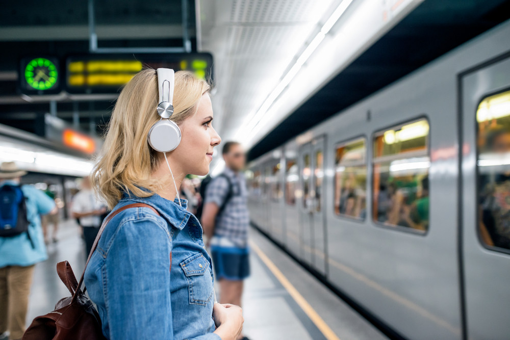 Beautiful young blond woman in denim shirt with earphones