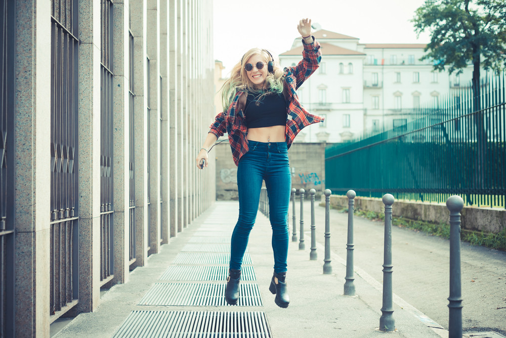 beautiful young blonde hair woman hipster jumping and dancing listening music in the city
