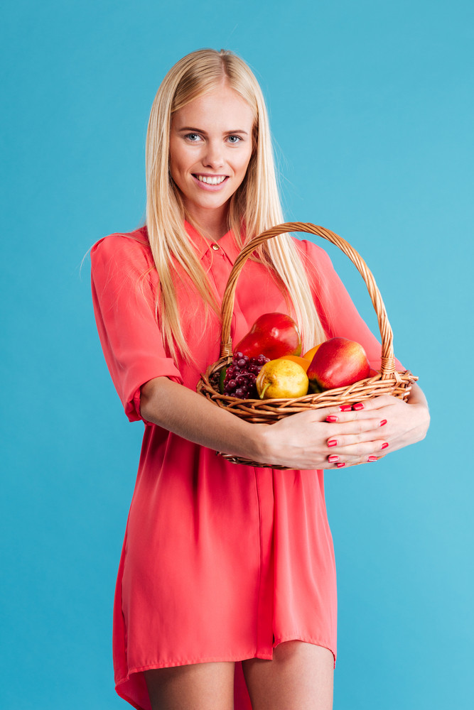 Beautiful young blonde woman with a wicker basket full of fruits isolated on a blue background