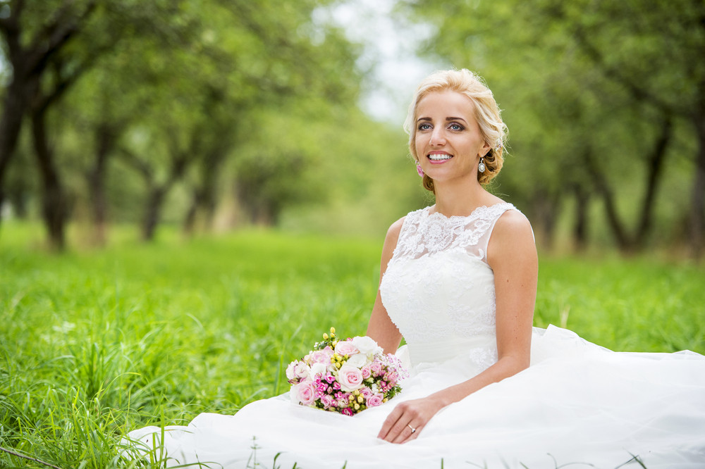 Beautiful young bride in wedding dress sitting in the grass