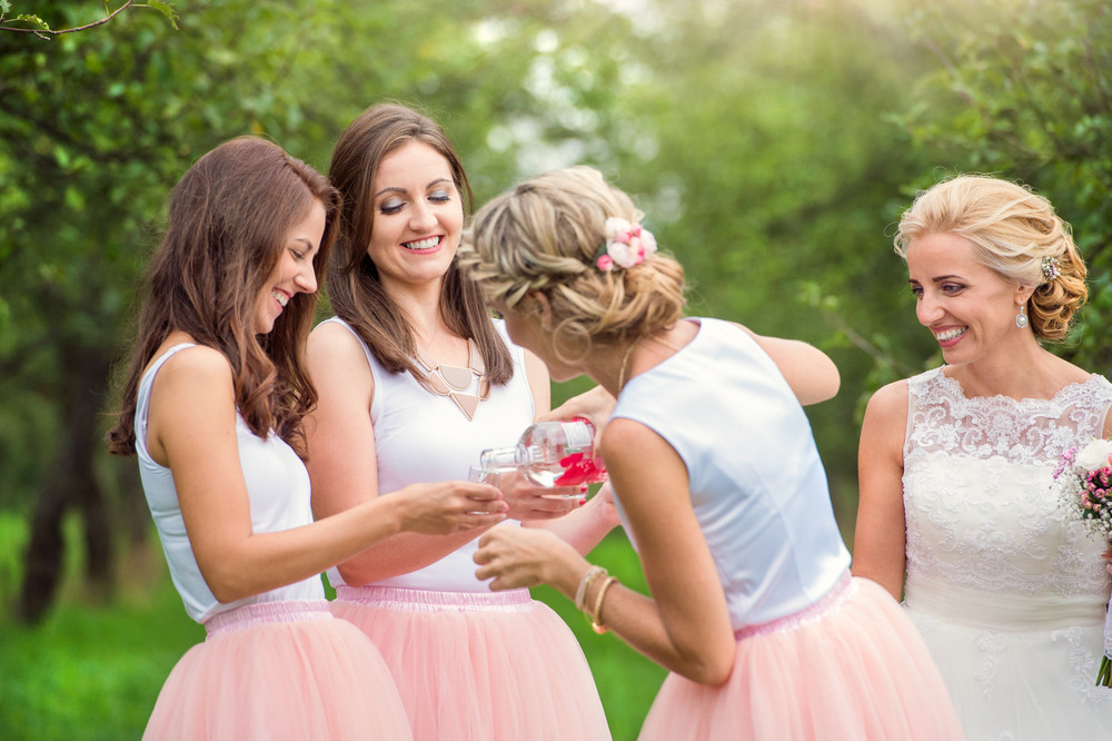 Beautiful young bride with her bridesmaids outside in nature