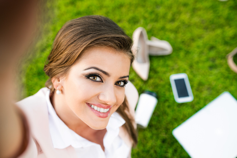 Beautiful young business woman sitting in a park