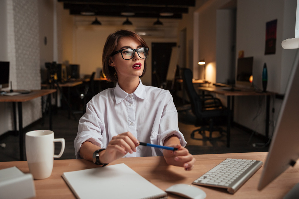 Beautiful young businesswoman in glasses sitting and working with computer in office