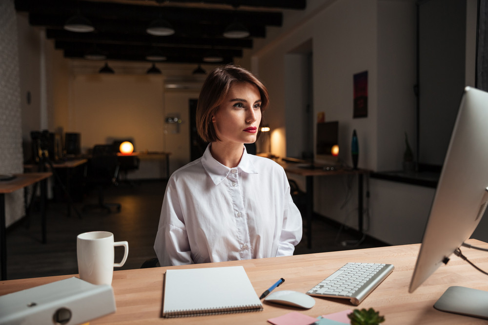 Beautiful young businesswoman sitting at the table and working in office
