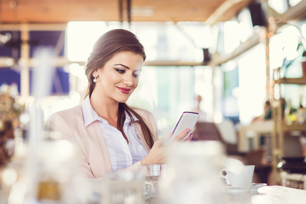 Beautiful young businesswoman with smart phone in cafe