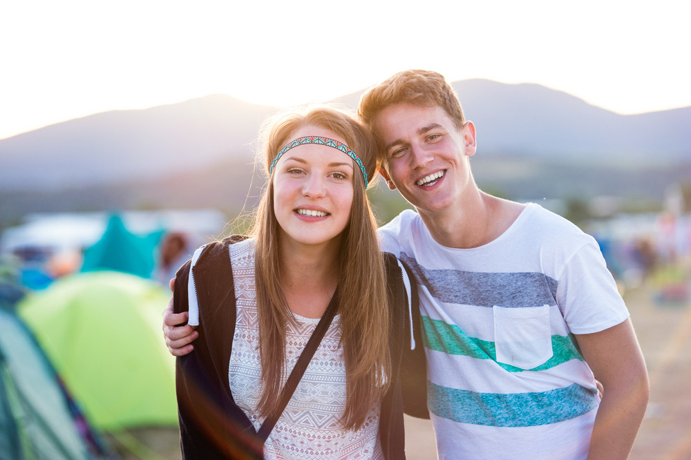 Beautiful young couple at summer tent festival enjoying themselves