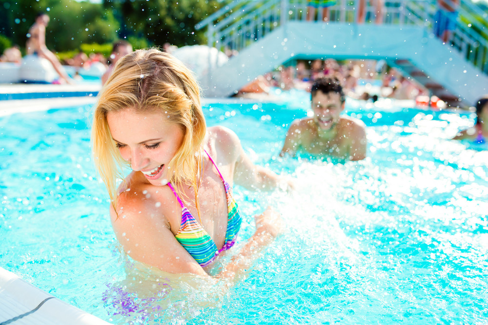 Beautiful young couple having fun outside in the swimming pool