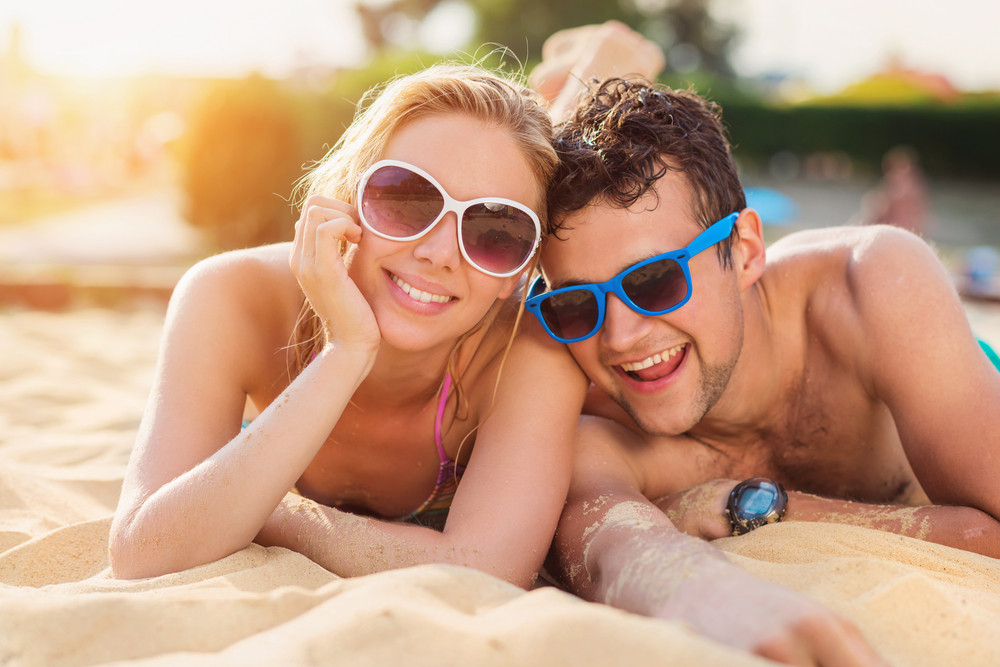 Beautiful young couple having fun outside on the beach