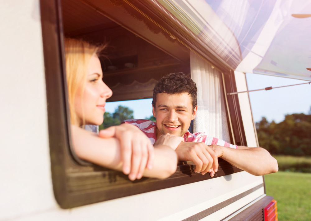 Beautiful young couple in a camper van on a summer day