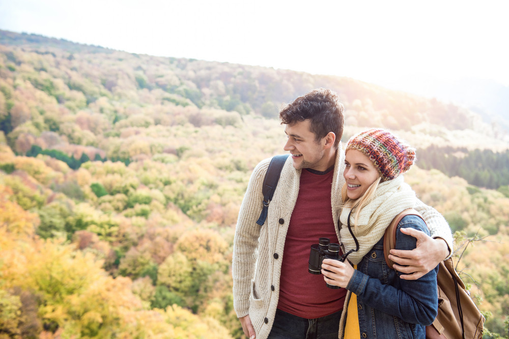 Beautiful young couple on a walk in sunny autumn forest, woman holding binoculars