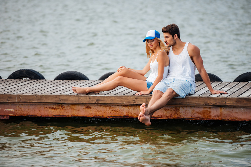 Beautiful young couple sitting barefoot and talking on pier