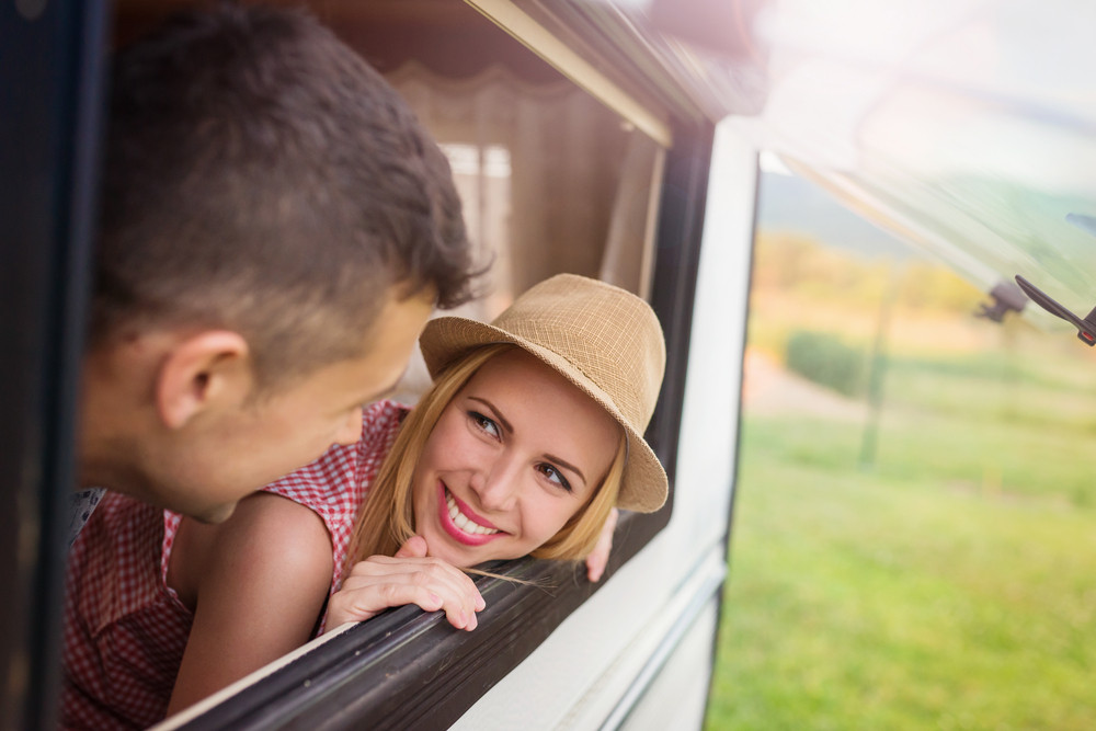 Beautiful young couple sitting in a camper van on a summer day