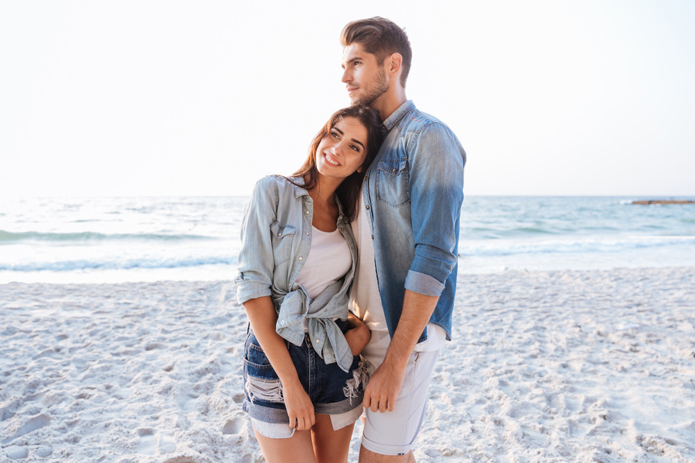 Beautiful young couple standing and dreaming on the beach together