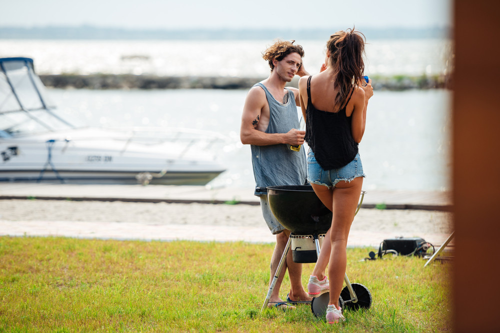 Beautiful young couple standing and frying meet on barbeque grill outdoors