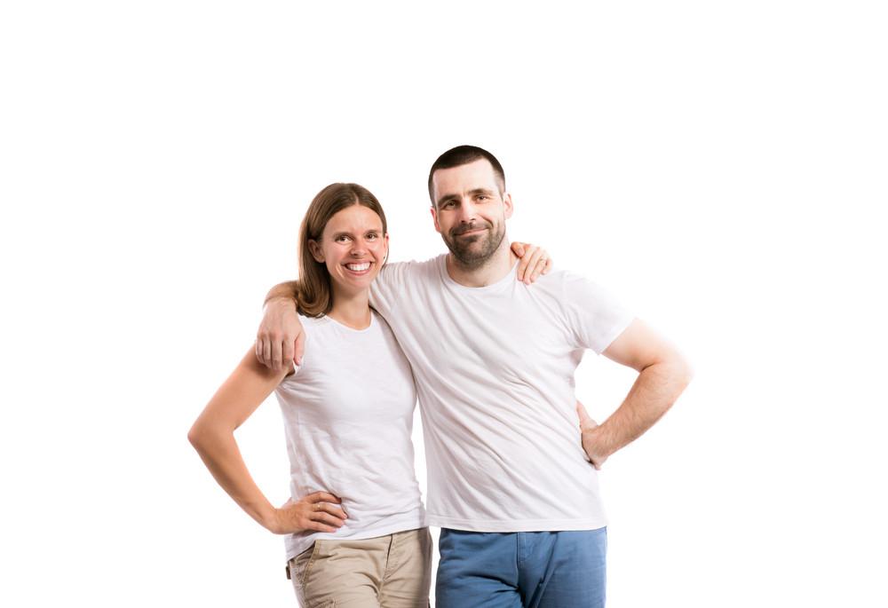 Beautiful young couple. Studio shot on gray background.