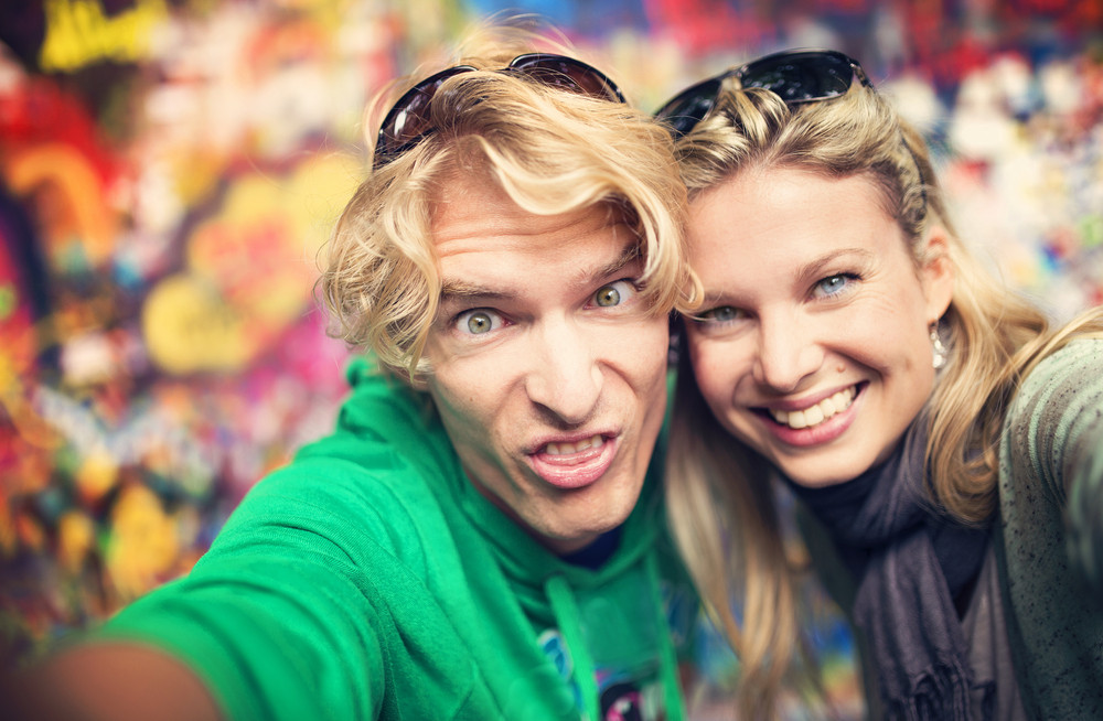 Beautiful young couple taking selfie of themselves as they make funny faces
