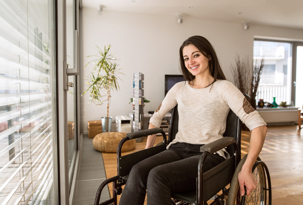 Beautiful Young Disabled Woman In Wheelchair At The Window