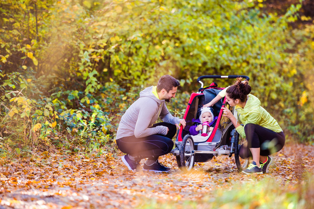 Beautiful young family with baby in jogging stroller outside in autumn nature