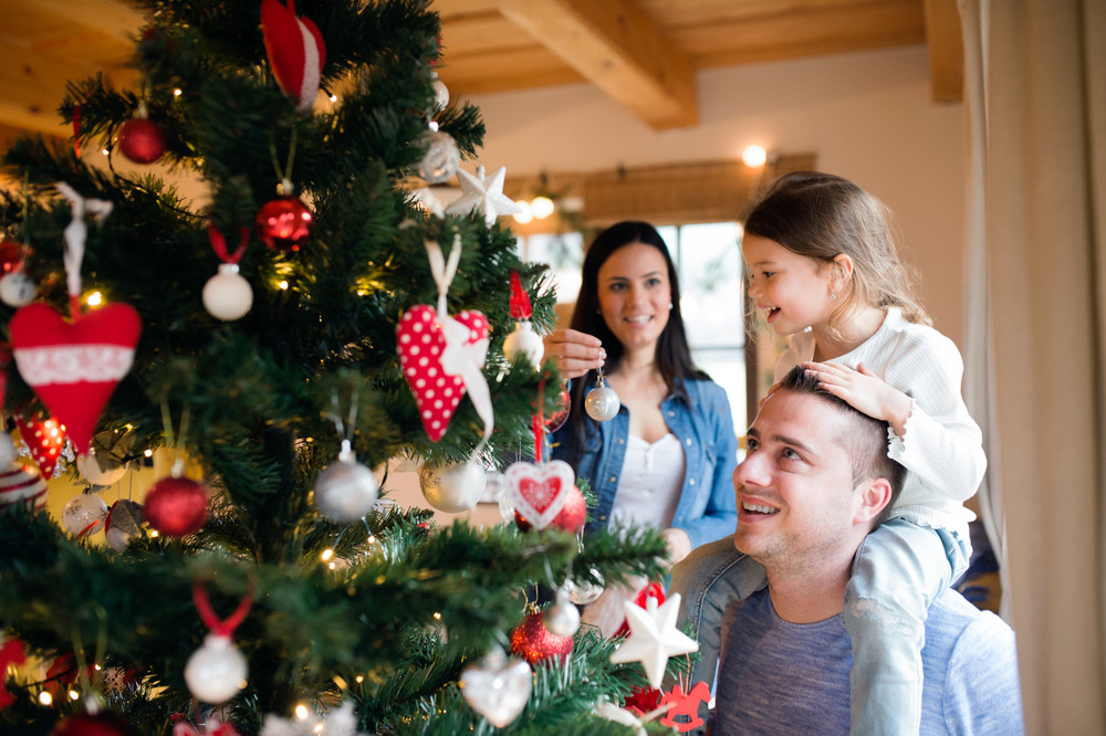 Beautiful young family with little girl decorating Christmas tree at ...