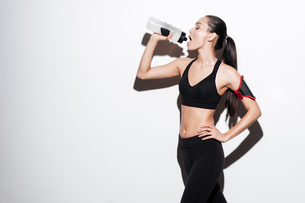 Beautiful young fitness woman standing and drinking water over white background