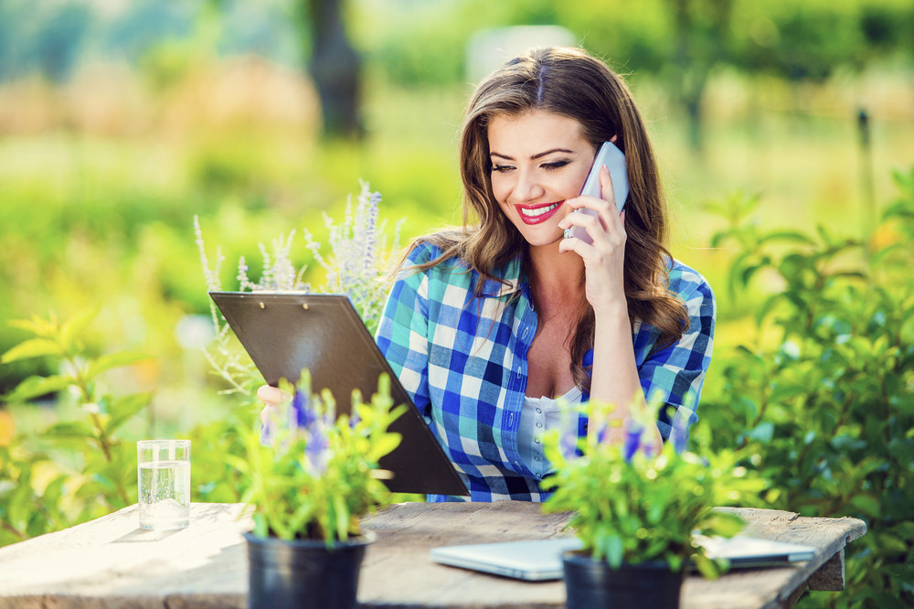 Beautiful young garden manager with a smartphone working outside