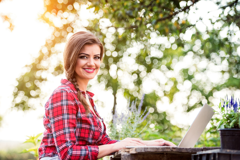 Beautiful young garden manager with notebook working outside