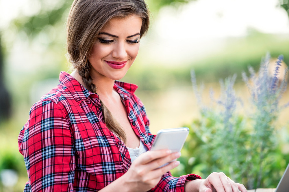 Beautiful young garden manager with smartphone working outside