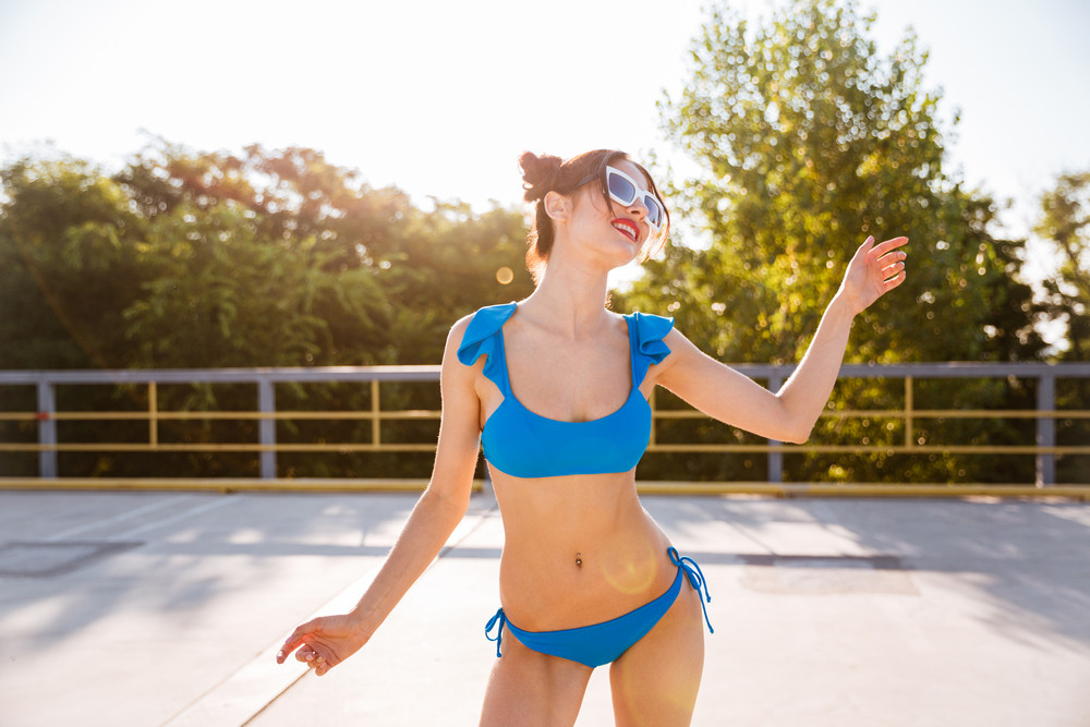 Beautiful young girl in blue swimsuit and sunglasses posing outdoors on the open road