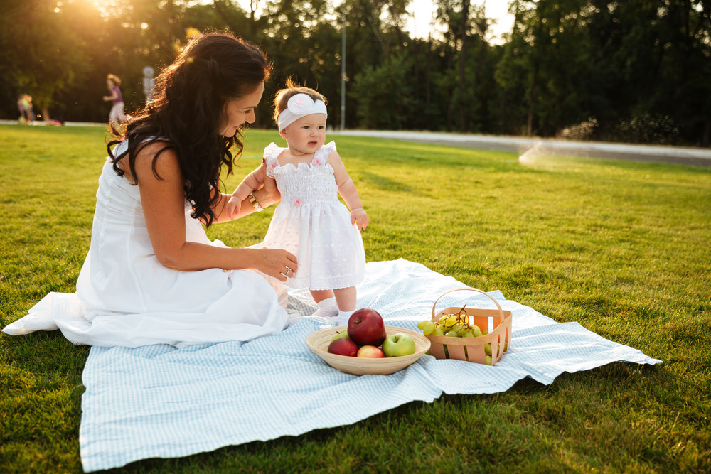 Beautiful young mother and her little daughter on picnic