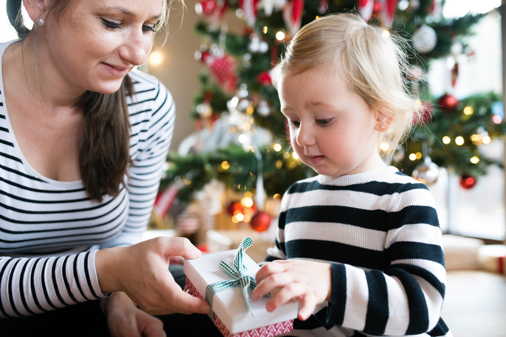 Beautiful young mother giving her cute litte daughter Christmas ...