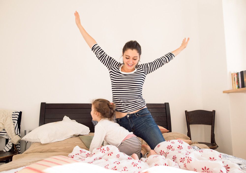 Beautiful young mother having fun with her daughter on bed in her bedroom