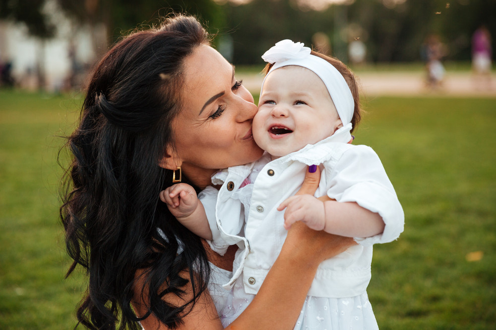 Beautiful young mother kissing her little daughter in park