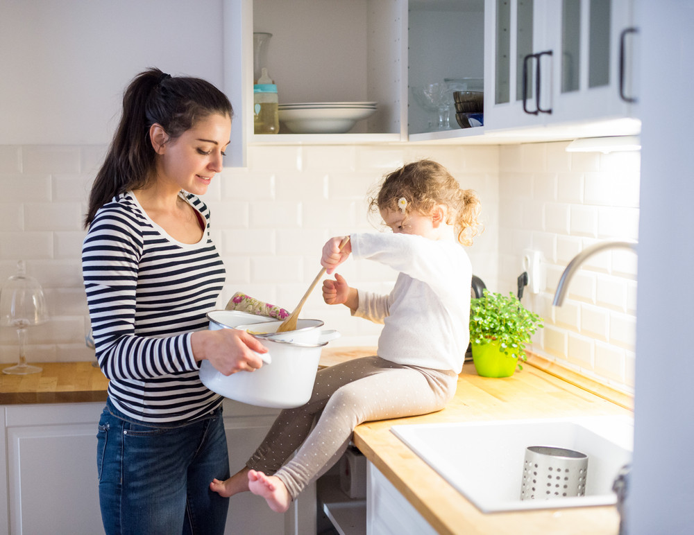 Beautiful young mother with her cute little daughter in the kitchen, cooking together, mixing something in a pot.