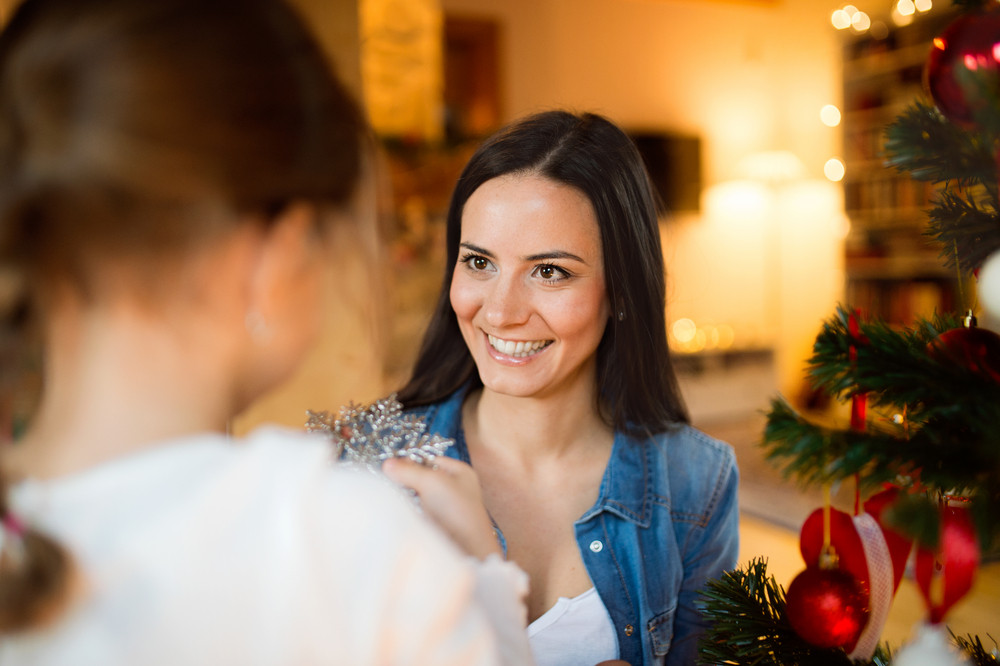 Beautiful young mother with little daughter at home decorating Christmas tree together.
