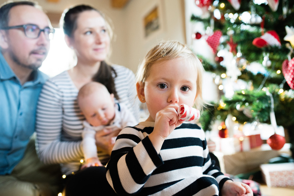 Beautiful young parents with baby son and cute daughter at Christmas tree blowing party whistle