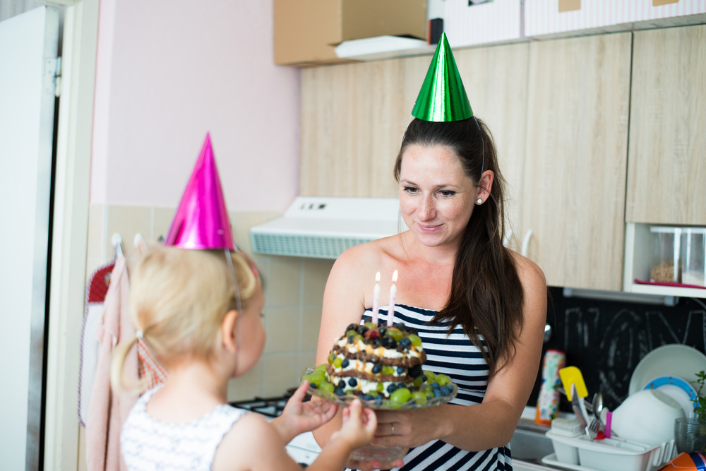 Beautiful young smiling mother giving her daughter fruit birthday cake with two candles. Colorful party hats on heads.