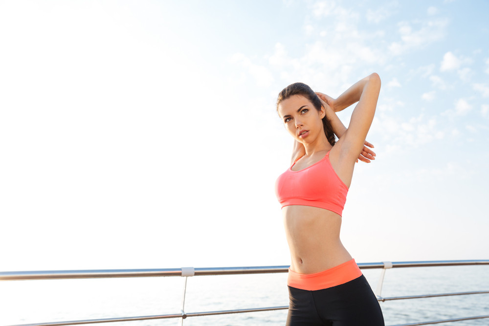 Beautiful young sportswoman standing and stretching arms on pier