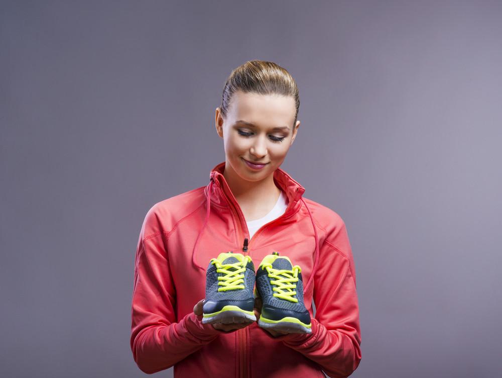 Beautiful young sportswoman. Studio shot on gray background.