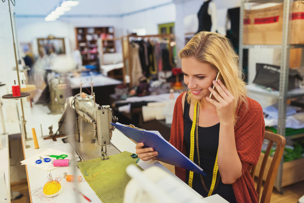 Beautiful young tailor woman with smart phone ordering new supplies