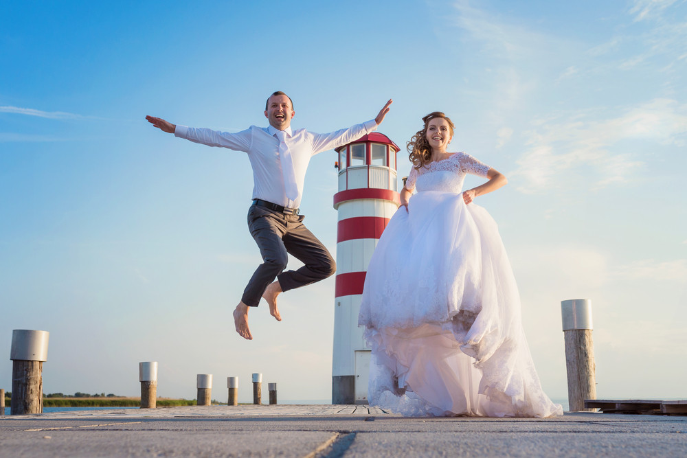 Beautiful young wedding couple on the pier in front of lighthouse